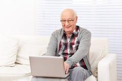 Starszy mężczyzna z komputerem zdjęcia royalty free