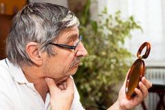 Starszy mężczyzna z lustrem zdjęcie royalty free
