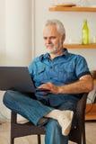 Starszy mężczyzna z notatnika obsiadaniem przy kuchnią fotografia royalty free