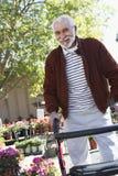 Starszy mężczyzna Z odprowadzenie ramą Przy ogródem botanicznym zdjęcia stock