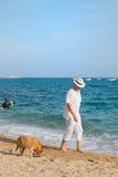 Starszy mężczyzna z psem przy plażą obraz royalty free