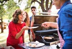 Starszy mężczyzna z rodziną i przyjaciółmi gotuje jedzenie na grillu na partyjnym outside fotografia royalty free