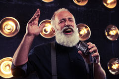 Starszy męski czuciowy szczęśliwy podczas gdy śpiewający jazz Zdjęcie Stock