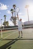 Starszy męski gracz w tenisa bawić się na sądzie Obrazy Royalty Free
