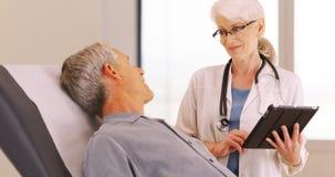 Starszy męski pacjent opowiada z lekarką o jego zdrowie koncernach Zdjęcie Stock
