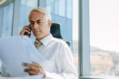 Starszy męski przedsiębiorca pracuje przy jego biurem Zdjęcie Royalty Free