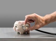 Starszy męski ręki mienia stetoskop na prosiątko banku Obrazy Royalty Free