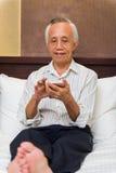 Starszy męski relaksować z telefonem Zdjęcie Stock