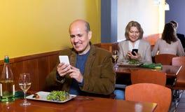 Starszy męski biznesmen z jedzeniem i smartphone Fotografia Royalty Free