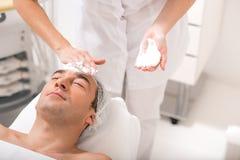 Starszy męski klient dostaje twarzowego skóry traktowanie Zdjęcia Royalty Free