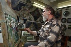 Starszy malarz z brodą i szkłami rysuje kwiatu obrazek nafcianą farbą w sztuka warsztacie obraz stock