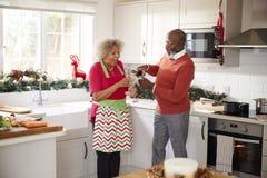 Starszy murzyna dolewania szampan dla jego partnera w kuchni podczas gdy przygotowywający gościa restauracji na święto bożęgo nar zdjęcie stock