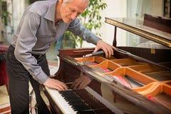 Starszy muzycznego instrumentu technik nastraja fortepianową klawiaturę Fotografia Royalty Free