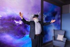 Starszy nowożytny mężczyzna używa VR szkła zabawiających out i wiszących Zdjęcia Royalty Free