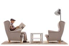 Starszy obsiadanie w czytaniu i karle gazeta zdjęcia royalty free