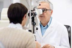 Starszy oko specjalisty spojrzenie w oftalmoskopie i wykonuje oko rev Fotografia Stock