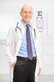 Starszy okulista pozuje w jego biurze fotografia royalty free