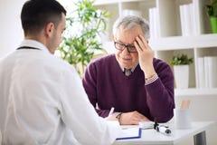 Starszy pacjent z bólami w kierowniczy potrzeby egzamininować obraz stock
