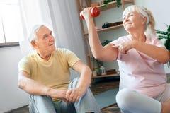 Starszy pary ćwiczenia opieki zdrowotnej obsiadanie z dumbbells pokazuje mięsień wpólnie w domu Fotografia Stock