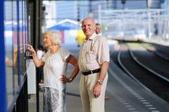 Starszy pary czekanie dla pociągu przy stacją kolejową Zdjęcie Stock