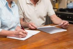 Starszy pary czytanie, writing i Zdjęcia Royalty Free