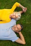 Starszy pary lying on the beach na trawie Zdjęcia Royalty Free