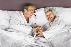 Starszy pary lying on the beach w łóżku obrazy stock