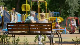 Starszy pary obsiadanie na ławce blisko boiska, dopatrywanie wnuków bawić się obraz royalty free
