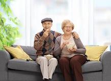 Starszy pary obsiadanie na łasowanie popkornie i kanapie Zdjęcia Stock