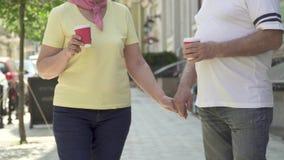Starszy pary odprowadzenie w miasta mienia kawie i rękach zbiory wideo