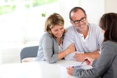 Starszy pary podpisywania kontrakt z pieniężnym advisor obraz stock