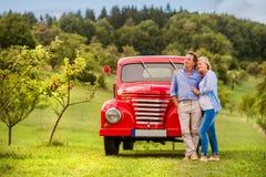 Starszy pary przytulenie, rocznik projektował czerwonego samochód, pogodna natura fotografia stock