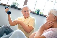 Starszy pary ćwiczenia opieki zdrowotnej obsiadanie z dumbbells pokazuje bicepsy wpólnie w domu Zdjęcie Stock