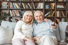 Starszy pary wpólnie w domu emerytury pojęcie ogląda tv mienia pilota kontrolera obraz royalty free