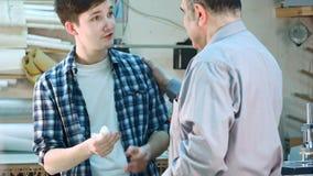 Starszy pracownik kłaść bandaż na ranie na palcu młody praktykant w ramowym warsztacie Obrazy Royalty Free
