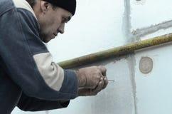 Starszy pracownik tworzy dziury w rozprężonej polistyren ścianie dla natępnej instalaci parasolowy dowel i musztrowania fotografia royalty free