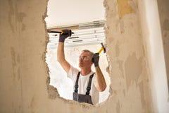 Starszy pracownik używa narzędzie przy contruction miejscem Fotografia Royalty Free