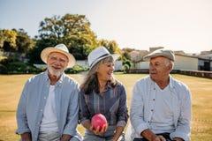 Starszy przyjaciele siedzi outdoors i śmia się fotografia royalty free