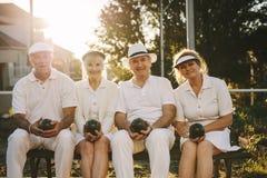 Starszy przyjaciele siedzi outdoors z boules w ręce obrazy royalty free