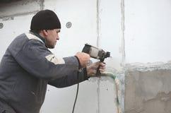 Starszy robociarz musztruje dziury w styrofoam ścianie dla natępnej instalaci plastikowy wzmacnia dowel _ obraz royalty free
