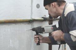 Starszy robociarz musztruje dziury w styrofoam ścianie dla natępnej instalaci plastikowy wzmacnia dowel _ zdjęcia stock