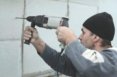 Starszy robociarz musztruje dziury w styrofoam ścianie dla natępnej instalaci plastikowy wzmacnia dowel _ fotografia royalty free