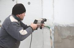 Starszy robociarz musztruje dziury w styrofoam ścianie dla natępnej instalaci plastikowy wzmacnia dowel _ obrazy royalty free