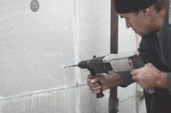 Starszy robociarz musztruje dziury w styrofoam ścianie dla natępnej instalaci plastikowy wzmacnia dowel _ obrazy stock