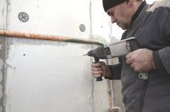 Starszy robociarz musztruje dziury w styrofoam ?cianie dla nat?pnej instalaci plastikowy wzmacnia dowel _ obraz stock