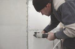 Starszy robociarz musztruje dziury w styrofoam ?cianie dla nat?pnej instalaci plastikowy wzmacnia dowel _ obrazy royalty free