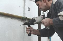 Starszy robociarz musztruje dziury w styrofoam ?cianie dla nat?pnej instalaci plastikowy wzmacnia dowel _ fotografia royalty free