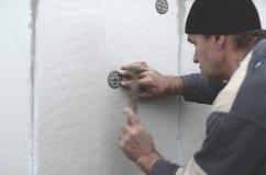 Starszy robociarz zatyka dowel w plastikową parasolową górę w styrofoam ścianie Proces naprawianie rozprężony polistyren zdjęcie stock
