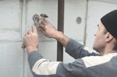 Starszy robociarz zatyka dowel w plastikową parasolową górę w styrofoam ścianie Proces naprawianie rozprężony polistyren zdjęcia stock