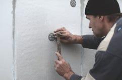 Starszy robociarz zatyka dowel w plastikową parasolową górę w styrofoam ścianie Proces naprawianie rozprężony polistyren obrazy royalty free